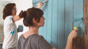 Frauen streichen Wand / Kunden zurückholen