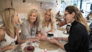 Eine Frau führt in einem Café Gespräche mit ihren Kundinnen / Artikel mehr über seine Kunden erfahren