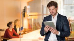 Ein Mann guckt auf sein Tablet und ist zufrieden /Eintrag in Das Örtliche